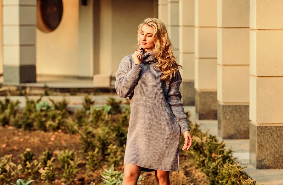 Young woman flexing her elongated sweatshirt tunic dress.